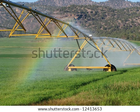 rainbow in the spray of a pivot irrigation system in a green field - stock photo