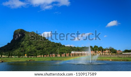 Rainbow in water fountain and Green Mountain at Pattaya, Thailand. - stock photo