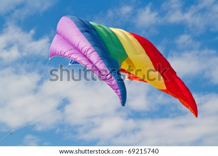 Rainbow kite floats in beautiful blue sky