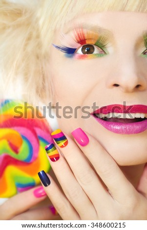 Rainbow manicure on artificial nails square shape, with a Lollipop in hand and colorful makeup.