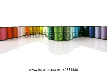 Rainbow of colorful thread spools on a white reflective background
