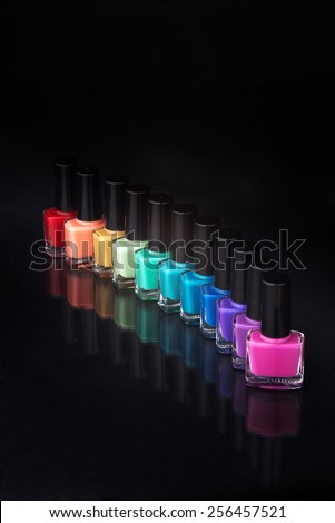 rainbow of nail polishes on a black background - stock photo