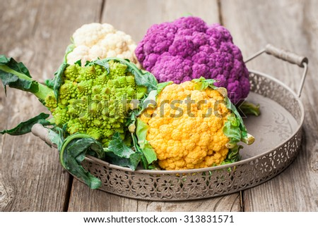 Rainbow of organic cauliflower and Romanesco broccoli on wooden table. Also available in vertical format. - stock photo