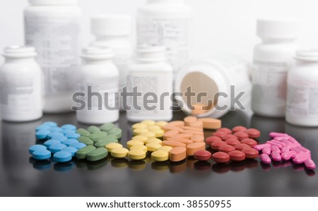 rainbow of prescriptions drugs with white bottles on black - stock photo