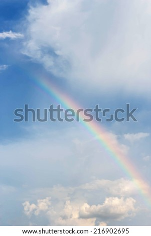 Rainbow on a background of blue sky and clouds - stock photo