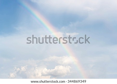 Rainbow on a background of blue sky and clouds, blur - stock photo