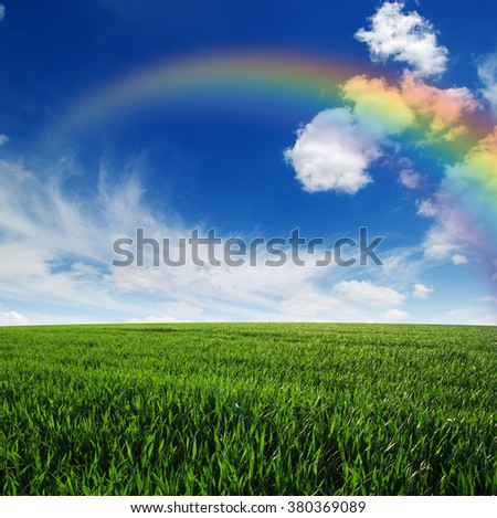 Rainbow on landscape with green field