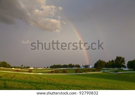Rainbow over a horse farm - stock photo
