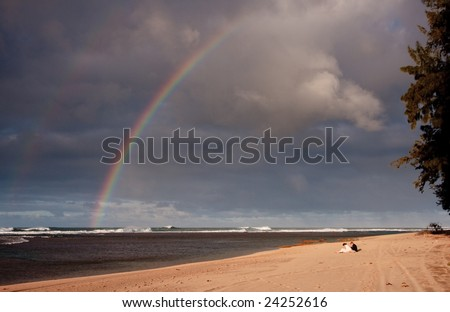 Rainbow over a sandy beach with a couple in the foreground