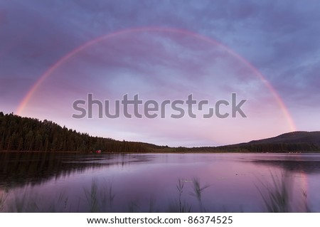 Rainbow over a swedish lake with windblown reed in the foreground - stock photo