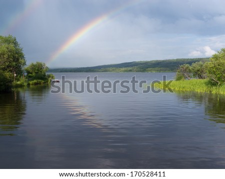 Rainbow over calm water of northern boreal forest taiga lake, northern British Columbia, Canada - stock photo