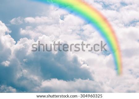 Rainbow over cloudy sky - stock photo