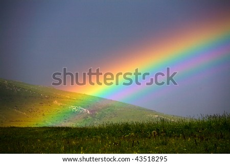 rainbow over grass filed - stock photo