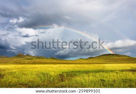 Rainbow over siberian steppe with Cumulus Clouds - stock photo