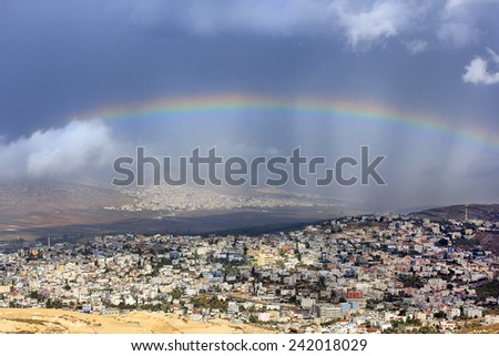 rainbow over the arab village Cana of Galilee ( Kafr Kanna ) in Israel , place where Christ showed first miracle - stock photo