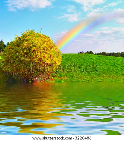 Rainbow over the green meadow - stock photo