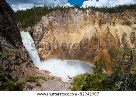 Rainbow over the waterfall in the Grand Canyon of the yellowstone national park, WY - stock photo