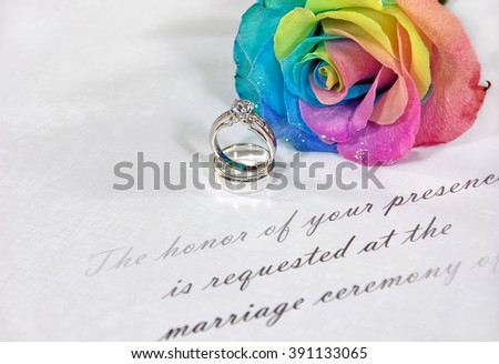 rainbow rose and wedding rings on traditional wedding invitation - stock photo