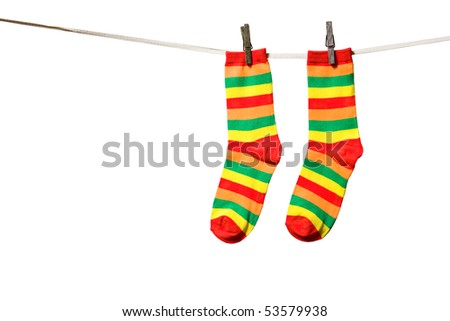 Rainbow socks hanging on a rope - stock photo