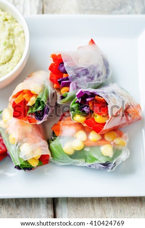 rainbow spring rolls with avocado white bean hummus on white wood background. toning. selective focus