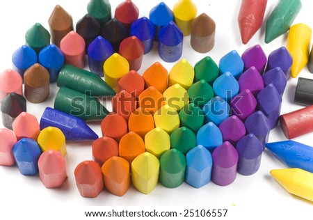 Rainbow stacked wax crayons on colored background