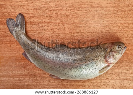 Rainbow trout bent on brown wooden surface. Shallow depth of field - stock photo