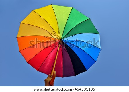 Rainbow umbrella in hand of a man on blue sky