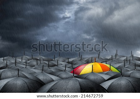 rainbow umbrella in mass of black umbrellas  - stock photo