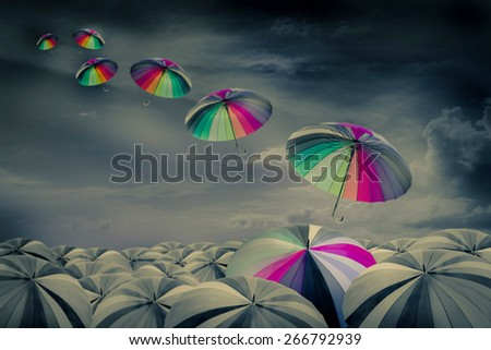 rainbow umbrella in the mass of black umbrellas - stock photo