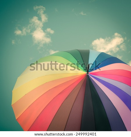 Rainbow umbrella on sky background, vintage style - stock photo