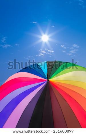 Rainbow umbrella on sky background, vintage style - stock photo