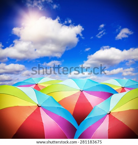 Rainbow umbrellas against the background of the sunny sky. focus on the foreground umbrellas - stock photo