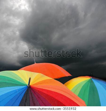 Rainbow Umbrellas Under Storm Clouds - stock photo