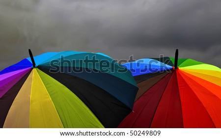Rainbow Umbrellas Under Storm Clouds - stock photo