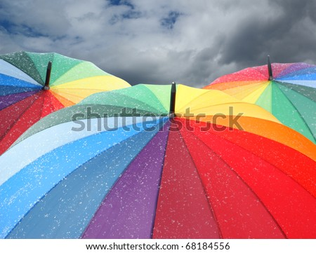 Rainbow umbrellas with snowflakes on dramatic sky background - stock photo