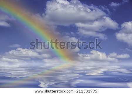 rainbow with blue sky clouds reflections - stock photo