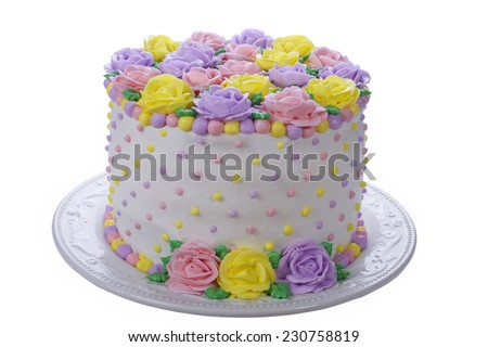 Rainbow Yellow, Pink, Purple butter cream frosting handmade roses on a round cake frosted with white icing and embellished with yellow, pink and purple dots of buttercream frosting. Isolated. - stock photo