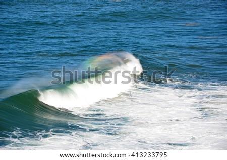 Rainbows on ocean wave spray - stock photo