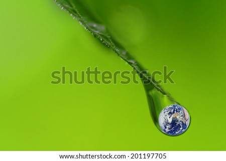 raindrop closeup with the planet earth inside on green background ( Elements of this image furnished by NASA ) - stock photo