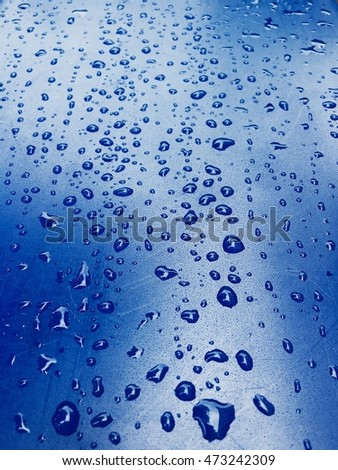 Raindrop on blue glass window, abstract background.