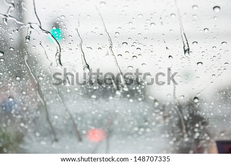 raindrop on windshield with green light traffic sign and other car background - stock photo