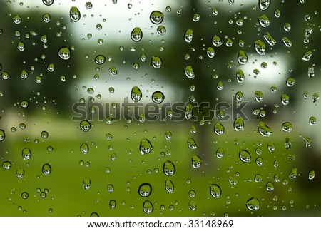 Raindrops collecting on a window on a gloomy and rainy day. - stock photo