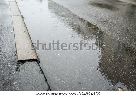 Raindrops in a puddle at a street with curb