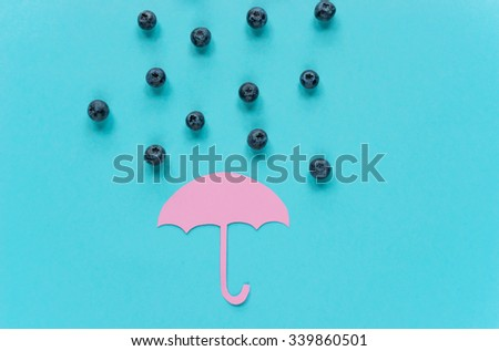 raindrops in the form of a blueberry above paper umbrella - stock photo