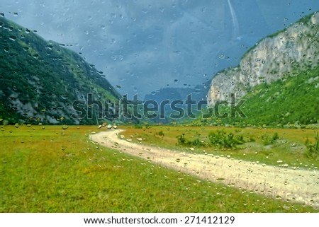 raindrops on a car glass, beyond a blurry view of the dirt road in the Komarnica Canyon, Montenegro   - stock photo