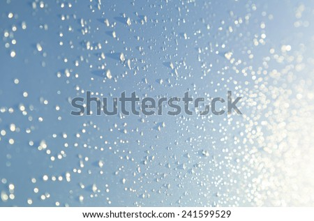 Raindrops on a shiny surface in the sunlight. Shallow D.O.F. - stock photo