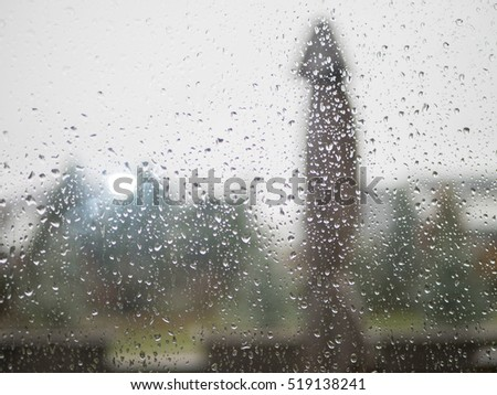 Raindrops on a steamy patio glass door looking out at a suburban street in Fall.  Shallow Depth of Field.