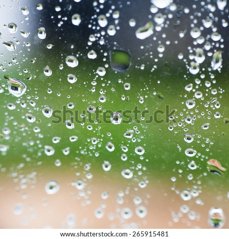 Raindrops on a window on a natural green and brown background - stock photo