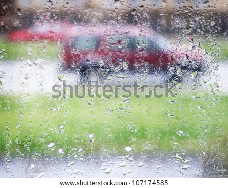 Raindrops on a window pane with a red car in the background, Sweden. - stock photo