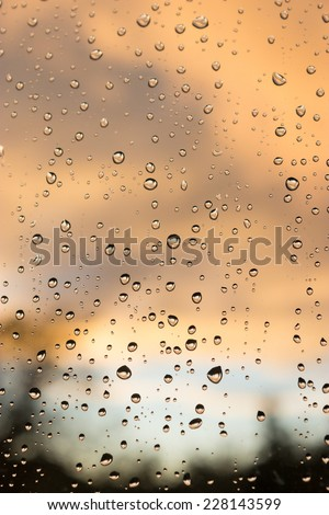 Raindrops on a Window, with a dramatic orange and mauve sky behind. - stock photo